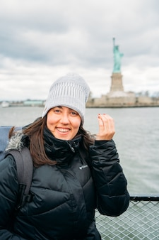 Porträt einer schönen reisenden frau, die mit der freiheitsstatue posiert - vertikales bild