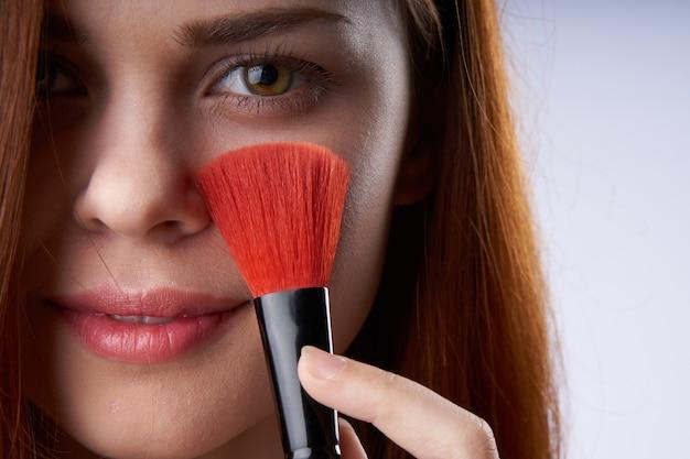 Porträt einer schönen rothaarigen frau mit make-up pinsel