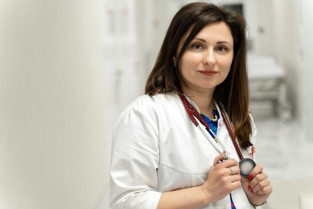 Porträt einer schönen ruhigen brünetten ärztin mit stethoskop am hals, die mit freude in die kamera schaut und in der halle des krankenhauses lächelt