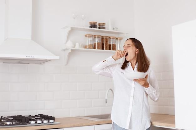 Porträt einer schönen schläfrigen dunkelhaarigen jungen erwachsenen frau, die in der küche frühstückt, mit erhobenem arm steht, gähnt und den mund mit der hand bedeckt.