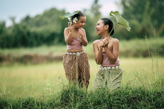 Porträt einer schönen schwester und einer jungen schwester in traditioneller thai-kleidung und weiße blume auf ihr ohr, lotusblatt in der hand haltend, sie lachen zusammen mit glücklichem reisfeld, kopienraum
