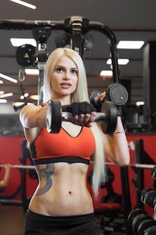 Porträt einer schönen sexy frau in sportkleidung im fitnessstudio gekleidet