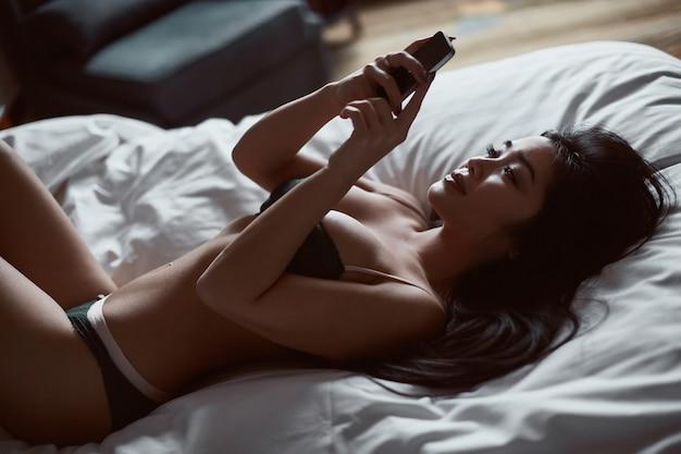 Porträt einer schönen sinnlichen asiatischen frau mit telefon