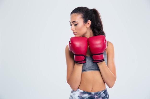 Porträt einer schönen sportfrau, die in der verteidigungshaltung mit den boxhandschuhen steht, die auf einer weißen wand lokalisiert werden