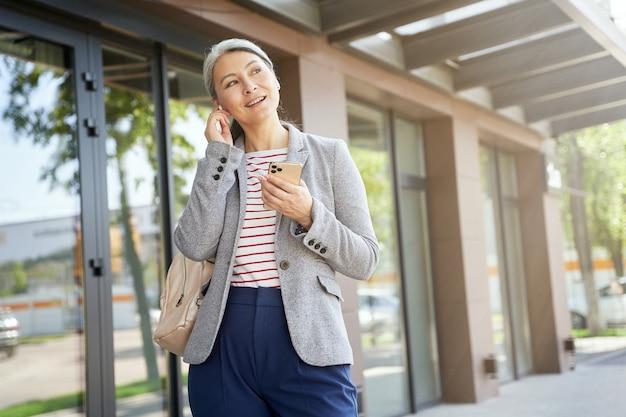 Porträt einer schönen und glücklichen frau, die drahtlose kopfhörer trägt und mit dem smartphone spricht