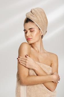 Porträt einer schönen vornehmen jungen frau nach dem spa, das in handtuch bedeckt steht.