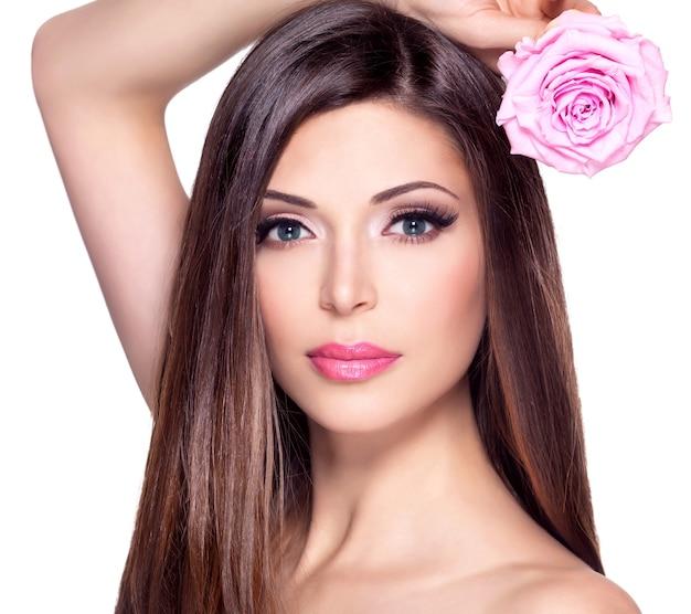 Porträt einer schönen weißen hübschen frau mit langen glatten haaren und rosa rose im gesicht.