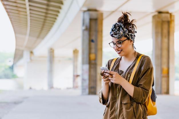 Porträt einer schönheit, die am intelligenten telefon schreibt