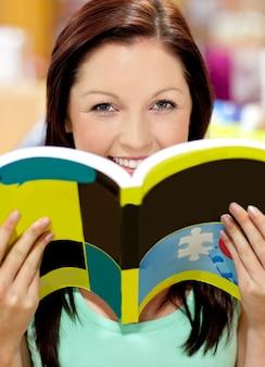 Porträt einer schönheit, die ein buch in einer bibliothek lächelt an der kamera hält