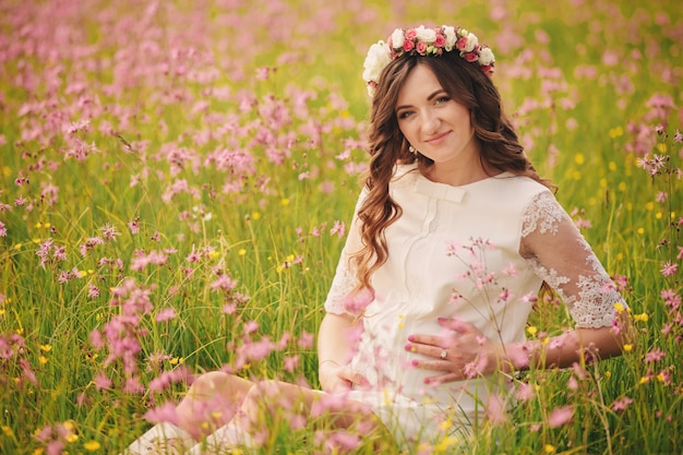 Porträt einer schwangeren frau, die im fieid der rosa blumen sitzt. junge schöne schwangere frau mit einem kranz auf ihrem kopf in der sonne. mutterschaft. frühling. speicherplatz kopieren. selektiver fokus