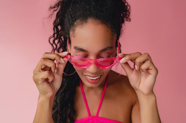 Porträt einer schwarzen afroamerikanerin im stylischen sommeroutfit rosa top auf rosa