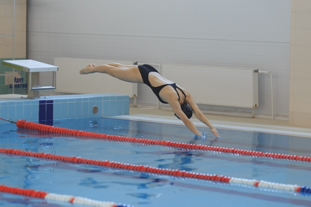 Porträt einer schwimmerin, die in ein hallenbad springt und eintaucht. sportliche frau.