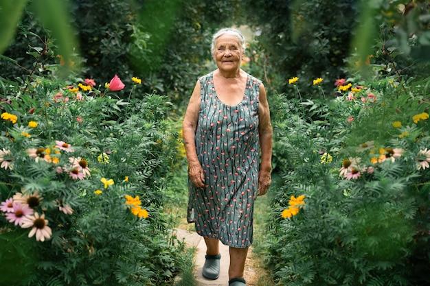 Porträt einer sehr alten frau, die im sommer mit blumen in ihrem garten spazieren geht. großeltern tag. hobbys für das ältere konzept.