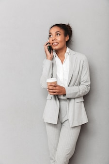 Porträt einer selbstbewussten afrikanischen geschäftsfrau, die anzug stehend, tasse kaffee haltend, am handy sprechend trägt