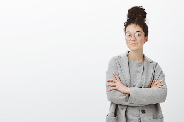 Porträt einer selbstbewussten geschäftsfrau mit lockigem haar, das in brötchen gekämmt ist, stilvolle brillen trägt, hände auf der brust gekreuzt hält und interessant blickt