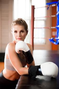 Porträt einer selbstbewussten jungen sportlerin, die in boxhandschuhen posiert.
