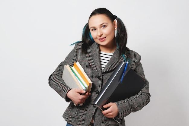 Porträt einer selbstbewussten jungen studentin, die bücher und ordner hält