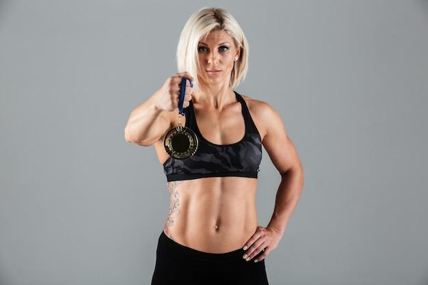 Porträt einer selbstbewussten sportlichen sportlerin, die eine medaille zeigt