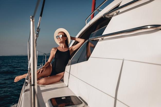 Porträt einer sexuell entzückenden niedlichen dame in einem schwarzen badeanzug, sonnenbrille und panama, posierend und sitzend auf einem weißen straßensegelboot