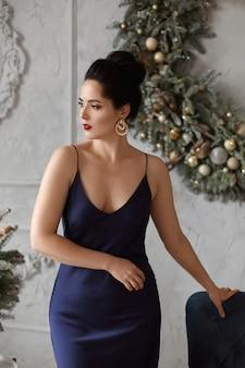 Porträt einer sexy jungen frau mit modischer frisur im dunkelblauen kleid posiert in dekoriert für silvesterparty-innenraum