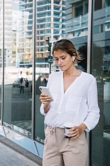 Porträt einer simsenden mitteilung der jungen geschäftsfrau auf smartphone