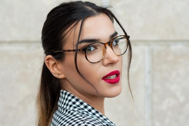 Porträt einer sinnlichen jungen brünetten sekretärin mit rot lackierten lippen und brille.