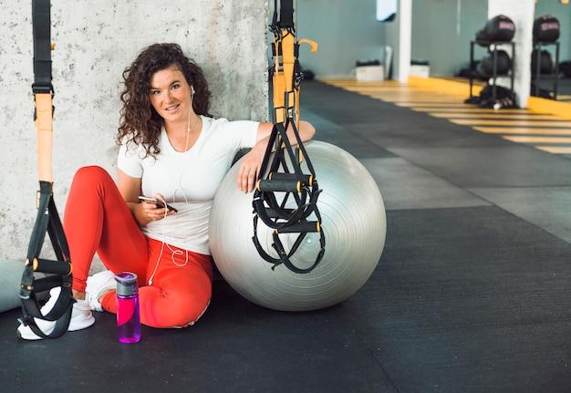 Porträt einer sitzfrau, die handy im fitness-club verwendet