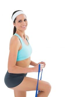 Porträt einer sitzfrau, die mit einem blauen yogagurt trainiert