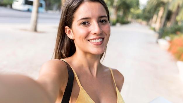 Porträt einer smiley-frau, die ein selfie nimmt