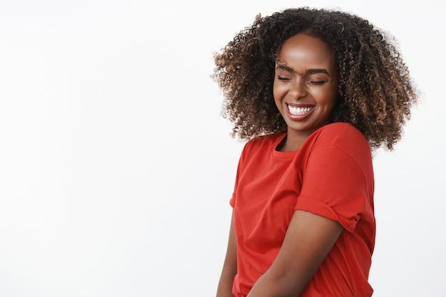 Porträt einer sorglosen und albernen, glücklichen, schönen und aufrichtigen afroamerikanischen jungen frau, die den kopf schwenkt und mit geschlossenen augen und einem breiten, fröhlichen lächeln über die weiße wand springt