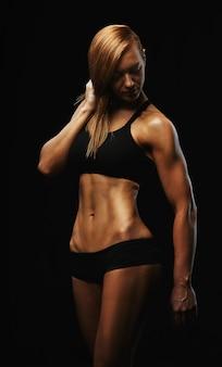Porträt einer sportfrau, auf einem dunklen hintergrund, sportmotivation, kopienraum.