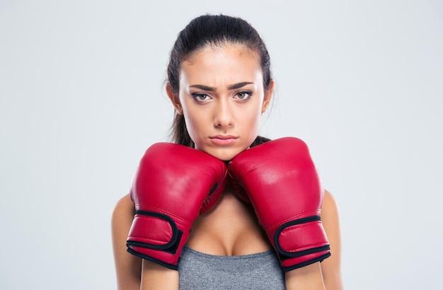 Porträt einer sportfrau, die in verteidigungshaltung mit den boxhandschuhen steht, die auf einer weißen wand lokalisiert werden