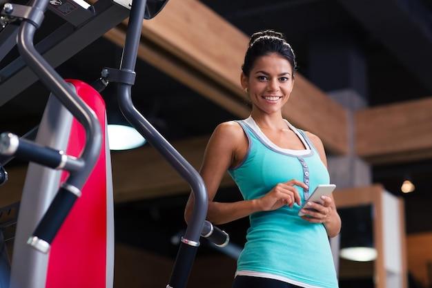 Porträt einer sportfrau, die mit smartphone in der turnhalle steht