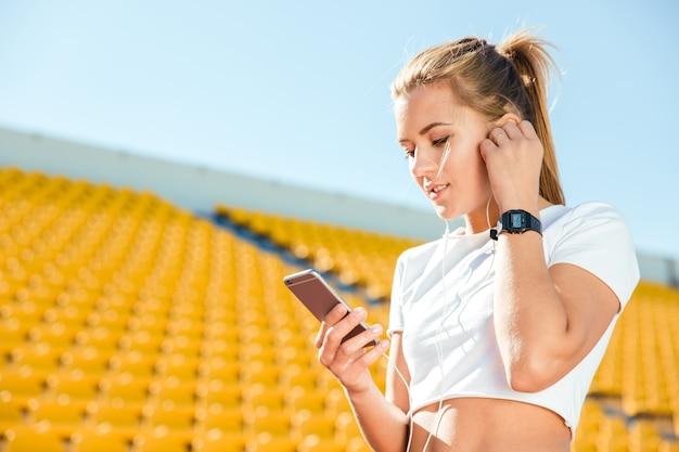 Porträt einer sportfrau, die smartphone auf stadion verwendet