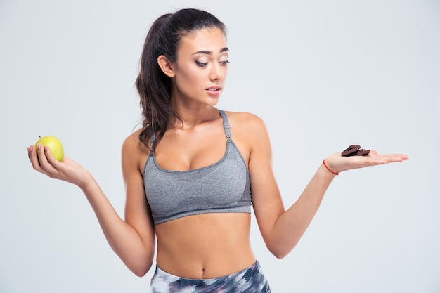 Porträt einer sportfrau, die zwischen apfel oder schokolade wählt lokalisiert auf einer weißen wand wählt