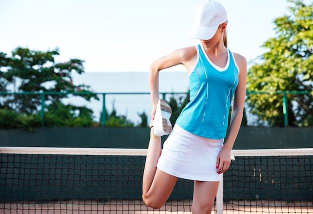 Porträt einer sportlerin, die draußen auf dem platz das bein ausdehnt
