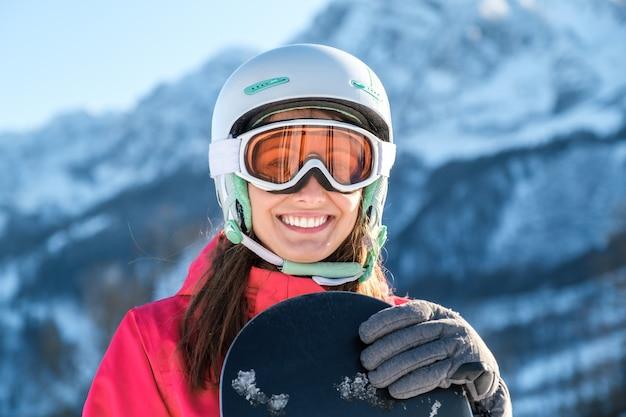 Porträt einer sportlerin, die helm und maske mit snowboard in der hand trägt kamera trägt
