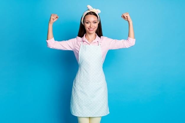 Porträt einer sportlichen putzfrau, die trizeps-hände-muskeln zeigt