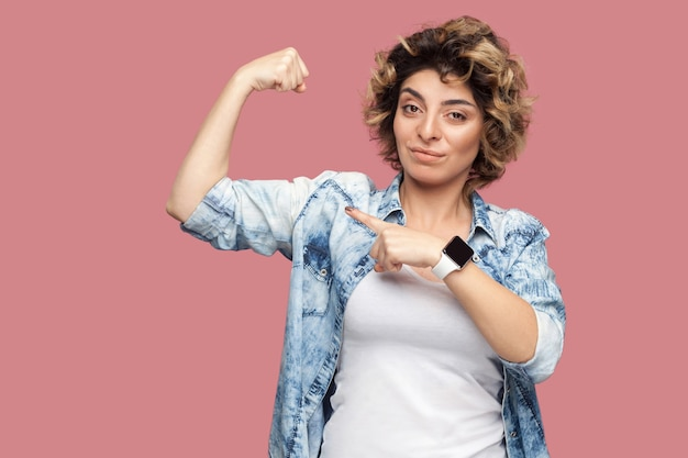 Porträt einer starken, stolzen jungen frau mit lockiger frisur in lässigem blauem hemd, die auf ihren bizeps steht und zeigt, um ihre unabhängigkeit oder ihren feminismus zu zeigen. indoor-studioaufnahme, isoliert auf rosa hintergrund.