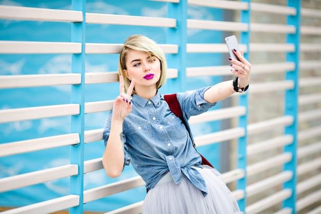Porträt einer stehenden frau mit kurzen blonden haaren, leuchtend rosa lippen und nacktem make-up, das selfie macht