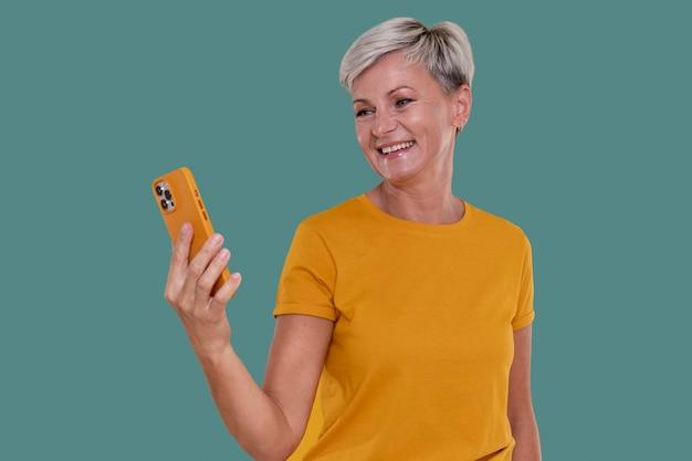 Porträt einer stilvollen älteren frau, die ihr telefon hält