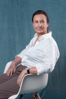 Porträt einer stilvollen älteren frau, die offiziell gekleidet auf einem stuhl sitzt und lächelt.