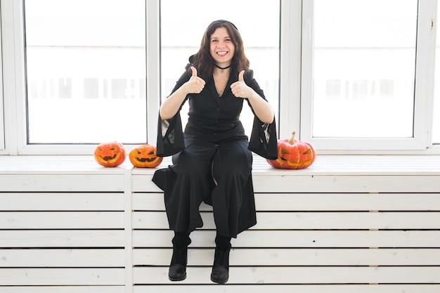 Porträt einer stilvollen brünetten frau, die daumen hoch geste mit halloween-kürbis auf hellem hintergrund zeigt