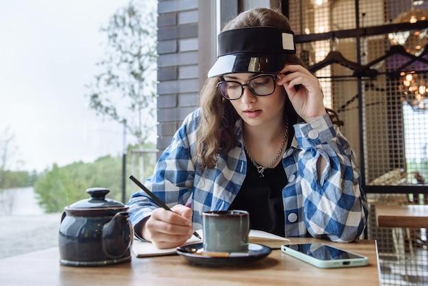 Porträt einer stilvollen brünetten frau mit brille, die in einem restaurant sitzt und mit einem stift in eine decke schreibt