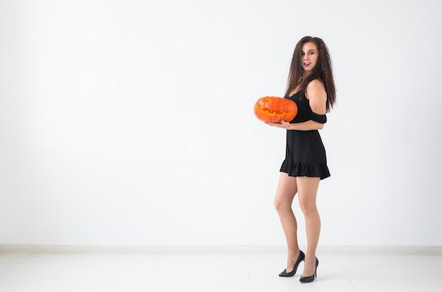 Porträt einer stilvollen brünetten frau mit halloween-kürbis über hellem hintergrund mit kopienraum