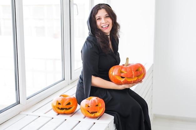 Porträt einer stilvollen brünetten frau mit halloween-kürbis über hellem hintergrund