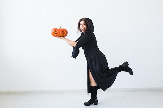 Porträt einer stilvollen brünetten frau mit halloween-kürbis über heller wand