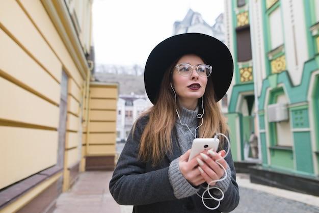 Porträt einer stilvollen frau, die musik in kopfhörern hört