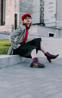 Porträt einer stilvollen jungen frau, die nahe dem grünen gras sitzt