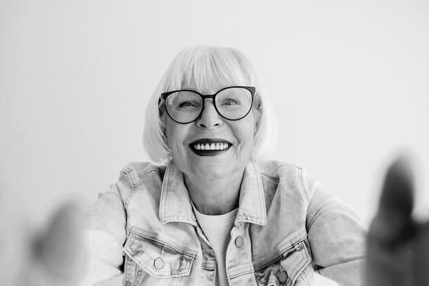 Porträt einer stilvollen seniorin mit grauem haar und in jeansjacke, die sie umarmt oder ein selfie macht